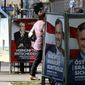 People walk between election posters of Alexander Van der Bellen and Norbert Hofer in Vienna on Sept. 12. (Associated Press)