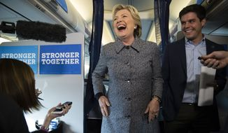 Democratic presidential candidate Hillary Clinton accompanied by traveling press secretary Nick Merrill speaks with members of the media on her campaign plane at Chicago Midway Airport in Chicago, Thursday, Sept. 29, 2016. (AP Photo/Matt Rourke)