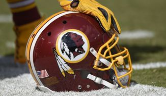 In this photo taken Sept. 18, 2016, a Washington Redskins helmet is seen on the sidelines during the first half of an NFL football game against the Dallas Cowboys in Landover, Md.  (AP Photo/Nick Wass) **FILE**