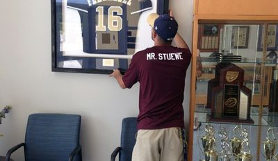 Alonso High School custodian Matt Stuewe hangs the school's remaining Jose Fernandez jersey after the other was stolen, Thursday, Sept. 29, 2016 in Tampa, Fla. Officials in Tampa said that a jersey worn by Fernandez in high school was missing following a candlelight vigil at his former high school. Officials at Alonso High School filed a police report and authorities are asking whoever took the jersey to return it.(Anastasia Dawson/Tampa Bay Times via AP)