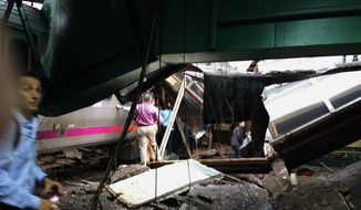 In a photo provided by William Sun, people examine the wreckage of a New Jersey Transit commuter train that crashed into the train station during the morning rush hour in Hoboken,, N.J., Thursday, Sept. 29, 2016. The crash caused an unknown number of injuries and witnesses reported seeing one woman trapped under concrete and many people bleeding. (William Sun via AP)