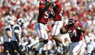 Alabama linebacker Tim Williams, left, defensive back Minkah Fitzpatrick, center and defensive lineman Dalvin Tomlinson celebrate after Fitzpatrick sacked Kent State quarterback Mylik Mitchell in the first half during an NCAA college football game, Saturday, Sept. 24, 2016, in Tuscaloosa, Ala. (AP Photo/Brynn Anderson)