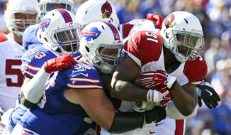 FILE - In this Sunday, Sept. 25, 2016, file photo, Arizona Cardinals running back David Johnson (31) is stopped by Buffalo Bills defenders Kyle Williams (95) and Zach Brown (53) during the second half of an NFL football game in Orchard Park, N.Y. Williams would prefer seeing much more consistent play before anyone begins assessing how much the Buffalo Bills defense has improved over last year. One good game followed by a dud just isn't going to cut it as Buffalo (1-2) prepares to play at New England (3-0) on Sunday.  (AP Photo/Bill Wippert, File)