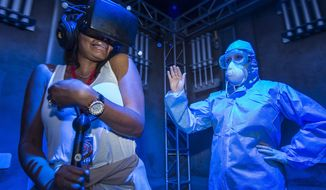 "In this Sept. 27, 2016 photo released by Universal Orlando, an unidentified woman, left, experiences the new immersive interactive experience, ""The Repository,"" at Universal Orlando Resort in Orlando, Fla. ""The Repository"" attraction is available on select nights through Oct. 31. (Octavian Cantilli/Universal Orlando via AP)"