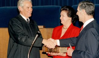 FILE - In this Feb. 6, 1987, file photo, Then Chief Justice of the California Supreme Court Malcolm Lucas, left, is given a congratulatory handshake by Governor George Deukmejian, right, to after being sworn in, while his wife, Joan Lucas, middle, looks on at the Senate Building in San Francisco, Calif. Lucas was sworn in after being nominated for the Chief Justice position by the governor. Former California Supreme Court Chief Justice Malcolm Lucas, who took the court's helm after three justices were voted out during a stormy period in the 1980s, has died. He was 89. Lucas died Wednesday, Sept. 28, 2016, at home in Los Angeles after battling cancer since early this year, his family said. (AP Photo/Jim Gerberich, File)