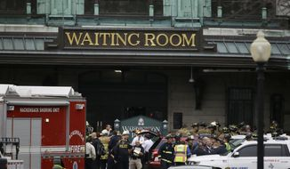 Emergency officials stand outside of the Hoboken Terminal following a train crash, Thursday, Sept. 29, 2016, in Hoboken, N.J. A commuter train crashed into the rail station during the morning rush hour, causing serious damage. (AP Photo/Julio Cortez)