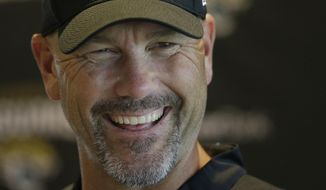 Jacksonville Jaguars head coach Gus Bradley smiles as he answers questions at a media conference following an NFL practice session at the Allianz Park rugby stadium in London, Friday, Sept. 30, 2016. The Jacksonville Jaguars are due to play the Indianapolis Colts at Wembley stadium in London on Sunday in a regular season NFL game. (AP Photo/Alastair Grant)