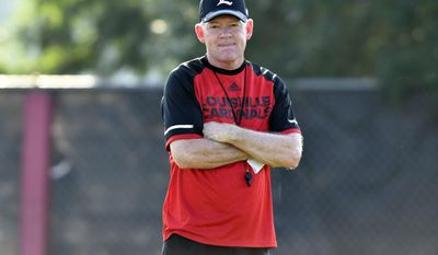 FILE - In this Aug. 5, 2016, file photo, Louisville coach Bobby Petrino looks on as his team goes through workouts during NCAA college football practice in Louisville Ky. Four and a half years after being fired by Long at Arkansas as a pariah, Petrino is rising again. His Louisville team is No. 3 in the country heading into showdown at No. 5 Clemson and his quarterback has gone from three-star prospect to Heisman Trophy front-runner in a little more than one season of college football. AP Photo/Timothy D. Easley, File)