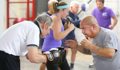 In this Monday, Sept. 19, 2016 photo, trainer Cisco Rodriguez, right,  helps first-time Parkinson's boxing participant Tom Pecsvaradi with a warm-up exercise at the Tazmanian Boxing Club in Carson City, Nev. (Jim Grant/Nevada Appeal via AP)