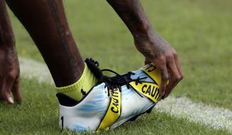 Washington Redskins wide receiver DeSean Jackson (11) wears cleats with a police caution tape theme during warm ups before an NFL football game against the Cleveland Browns Sunday, Oct. 2, 2016, in Landover, Md. (AP Photo/Chuck Burton)
