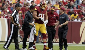 Washington Redskins outside linebacker Ryan Kerrigan (91) is helped off the field after an injury during the first half of an NFL football game against the Cleveland Browns, Sunday, Oct. 2, 2016, in Landover, Md. (AP Photo/Chuck Burton)