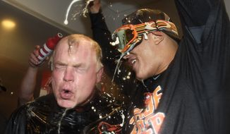 Baltimore Orioles manager Buck Showalter is doused with beer by Manny Machado in the visitors' clubhouse after the Orioles defeated the New York Yankees 5-2 in a baseball game to go to the playoffs, Sunday, Oct. 2, 2016, in New York. (AP Photo/Kathy Kmonicek)