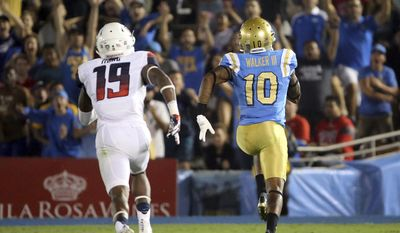UCLA wide receiver Kenneth Walker III carries a pass in for a touchdown as outruns Arizona'a DaVonte' Neal pursuit during the first half of an NCAA college football game Saturday, Oct. 1, 2016, in Pasadena, Calif. (AP Photo/Reed Saxon)