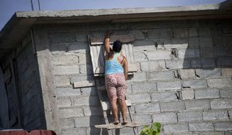 A woman shutters a window of her house before the arrival of Hurricane Matthew in Santiago, Cuba, Sunday, Oct. 2, 2016. Hurricane Mathew, one of the most powerful Atlantic hurricanes in recent history weakened a little on Saturday as it drenched coastal Colombia and roared across the Caribbean on a course that threatened Jamaica, Haiti and Cuba.(AP Photo/Ramon Espinosa)