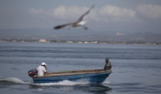 Fishermen sail on a boat at Port Royal in Kingston, Jamaica, Sunday, Oct. 2, 2016. Hurricane Mathew, one of the most powerful Atlantic hurricanes in recent history weakened a little on Saturday as it drenched coastal Colombia and roared across the Caribbean on a course that threatened Jamaica, Haiti and Cuba. (AP Photo/Eduardo Verdugo)
