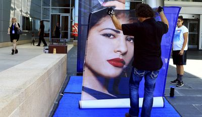 In this Thursday, Sept. 29, 2016 photo, a worker from the Production Resource Group unrolls a large photo of the late singer Selena Quintanilla for the unveiling of the MAC Selena makeup collection at the American Bank Center in Corpus Christi, Texas. Some fans of slain Tejano star Selena have flooded social media with complaints after her new makeup products sold out on their first day of online sales. MAC Cosmetics launched its Selena collection on Friday, Sept. 30 in Corpus Christi, Texas, the singer's hometown.  (Gabe Hernandez/Corpus Christi Caller-Times via AP)
