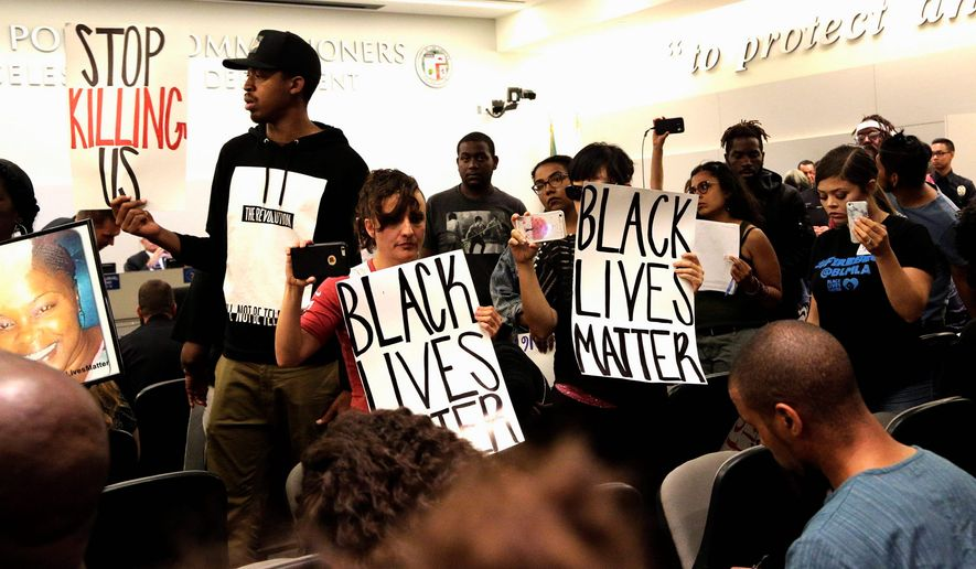 Black Lives Matter protesters demonstrate inside the board of Police Commissioners meeting in Los Angeles on Tuesday. Los Angeles police released surveillance video Tuesday showing an 18-year-old black suspect running from police while holding what appears to be a gun in his left hand just before he was fatally shot by officers in a death that has generated rowdy protests. (Associated Press)