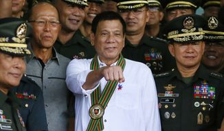 Philippine President Rodrigo Duterte, center, gestures with a fist bump as he poses with Philippine Army officers during his visit to its headquarters in suburban Taguig city east of Manila, Philippines Tuesday Oct. 4, 2016. U.S. and Philippine forces opened their first large scale combat exercises under President Duterte in uncertainty Tuesday after he said the drills will be the last in his six-year presidency partly to avoid upsetting China.(AP Photo/Bullit Marquez)