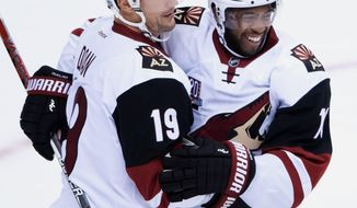 Arizona Coyotes' Shane Doan, left, and Anthony Duclair celebrate Doan's goal against the Vancouver Canucks during the second period of a preseason NHL hockey game in Vancouver, British Columbia, Monday, Oct. 3, 2016. (Darryl Dyck/The Canadian Press via AP)