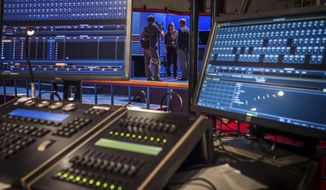 A CSPAN television crew is framed through an audio control board as they conduct an interview on the debate stage before the start of the vice-presidential debate at Longwood University in Farmville, Va., Tuesday, Oct. 4. 2016. (AP Photo/J. David Ake)