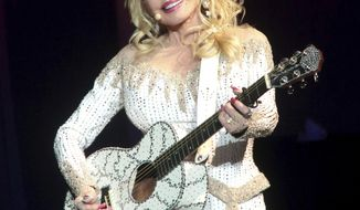 FILE - In this June 15, 2016 file photo, Dolly Parton performs in concert during her Pure & Simple Tour in Philadelphia. Parton will receive the Willie Nelson Lifetime Achievement Award at the 50th annual Country Music Association Awards in Nashville, Tenn., on Nov. 2. (Photo by Owen Sweeney/Invision/AP, File)