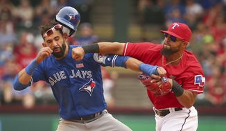 FILE - In this May 15, 2016, file photo, Toronto Blue Jays' Jose Bautista, left, is hit by Texas Rangers second baseman Rougned Odor, right, after Bautista slid into second in the eighth inning of a baseball game at Globe Life Park in Arlington, Texas. The Rangers and Blue Jays meet in an ALDS rematch. Game 1 is Thursday, Oct. 6. (Richard W. Rodriguez/Star-Telegram via AP, File)