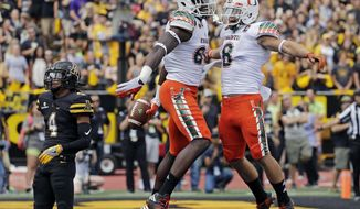 FILE - In this Sept. 17, 2016, file photo, Miami's David Njoku, center, celebrates with Braxton Berrios, right, after a touchdown catch as Appalachian State's Mondo Williams, left, watches during the first half of an NCAA college football game in Boone, N.C. The Miami Hurricanes have lost six straight to the Florida State Seminoles and nine of 11 in series that had a run in the late 1980s and early 1990s of often producing the most important college football game of the season. A real Hurrican is thgreatening the region and could disrupt Saturday's game. (AP Photo/Chuck Burton, File)