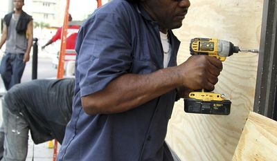 """Yorick Bain uses a drill to secure plywood over the windows of a Dunkin Donuts store in downtown Nassau, Bahamas, Tuesday, Oct. 4, 2016. The demand for materials such as plywood and sand caused many businesses to post """"sold out"""" signs as residents moved about the island preparing for the arrival of Hurricane Matthew which is is expected to impact all the islands of the Bahamas in the coming days on its way towards the Florida coastline. (AP Photo/Tim Aylen)"""