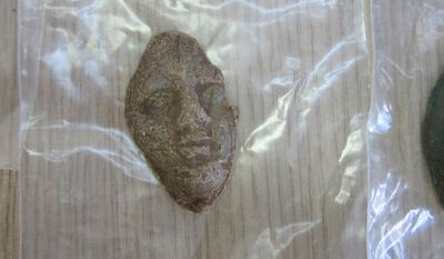 In this undated handout photo released by Greek Police on Wednesday, Oct. 5, 2016, a fragmentary metal artifact seized from a large antiquities-smuggling gang is displayed in the southwestern Greek city of Patras.  Police said Wednesday the gang allegedly exported thousands of Greek antiquities for sale through conniving European auction houses, or directly to private buyers.  Spokesman for the Patras police directorate, which headed the nationwide 14-month investigation, Haralambos Sfetsos said more than 50 people are thought to be involved in the criminal organization. (Greek Police via AP)