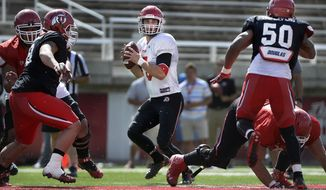 FILE - In this April 11, 2015, file photo, Utah quarterback Chase Hansen looks to throw during a scrimmage at Rice-Eccles Stadium in Salt Lake City. Redshirt sophomore Hansen was the quarterback of the future when he arrived at Utah, but circumstances pushed him to safety last season. What was thought to be a temporary move at the time has become a full-time job as the Utes now have one of the young budding safeties in the Pac-12. (Scott Sommerdorf/The Salt Lake Tribune via AP, File)
