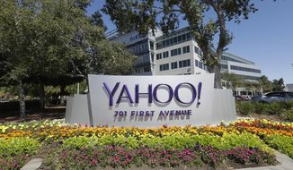 In this Tuesday, July 19, 2016, photo, flowers bloom in front of a Yahoo sign at the company's headquarters in Sunnyvale, Calif. (AP Photo/Marcio Jose Sanchez)