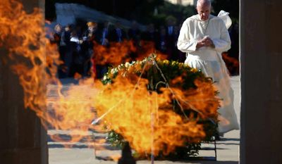 Pope Francis prays in front of the monument to the fallen for the independence, in Ganjlik, Azerbaijan October 2, 2016. Francis traveled to Azerbaijan on Sunday for a 10-hour visit aimed at encouraging the country's inter-religious harmony while likely overlooking criticism of a referendum that extends the president's term and powers. (Alessandro Bianchi/Pool Photo via AP)