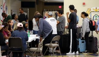 Families, with their bags packed, arrive to be checked into the shelter at North Charleston High School in North Charleston, S.C., Thursday, Oct. 6, 2016, in advance of Hurricane Matthew. (Grace Beahm/The Post And Courier via AP)