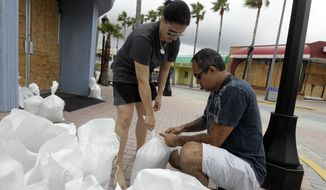 Miroslava Roznovjakova, left, and Ray Hayyat place sandbags in front of their store to guard against floodingThursday, Oct. 6, 2016, in Daytona Beach, Fla. Hurricane Matthew continues to churn its way toward Florida's east coast. (AP Photo/Chris O'Meara)