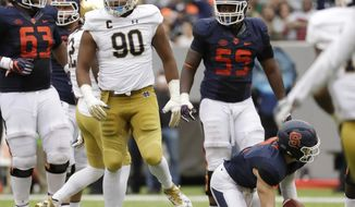 FILE - In this Oct. 1, 2016, file photo, Notre Dame defensive lineman Isaac Rochell (90) walks away after sacking Syracuse quarterback Eric Dungey (2) during the first half of an NCAA college football game at MetLife Stadium in East Rutherford, N.J. After three seasons of struggling playing a complicated scheme depending heavily on a core of players under defensive coordinator Brian VanGorder, coach Brian Kelly has changed things after firing his long-time friend by simplifying the defense and giving more players opportunities to get on the field in a 50-33 victory win over Syracuse where the Irish held the Orange to six points in the second half. (AP Photo/Julio Cortez, File)