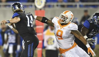 FILE - In this Oct. 31, 2015, file photo, Tennessee defensive end Derek Barnett sacks Kentucky quarterback Patrick Towles, left, during an NCAA college football game in Lexington, Ky. The matchup Saturday, Oct. 8, 2016, between No. 8 Texas A&M and No. 9 Tennessee potentially features two of the naton's top pass rushers in the Aggies' Myles Garrett and Barnett, assuming Garrett is healthy enough to play after sitting out last week's victory over South Carolina. (Adam Lau/Knoxville News Sentinel via AP, File)