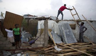 Residents repair their homes destroyed by Hurricane Matthew in Les Cayes, Haiti, Thursday, Oct. 6, 2016. Two days after the storm rampaged across the country's remote southwestern peninsula, authorities and aid workers still lack a clear picture of what they fear is the country's biggest disaster in years. (AP Photo/Dieu Nalio Chery)