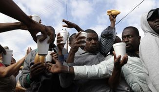 In this Oct. 3, 2016 photo, Haitian migrants receive food and drinks from volunteers as they wait in line at a Mexican immigration agency in Tijuana with the hope of gaining an appointment to cross to the U.S. side of the border. Many Haitians arriving at the Mexico-U.S. border are unaware of a new U.S. policy of putting them in deportation proceedings and detaining them while making efforts to fly them home. (AP Photo/Gregory Bull)