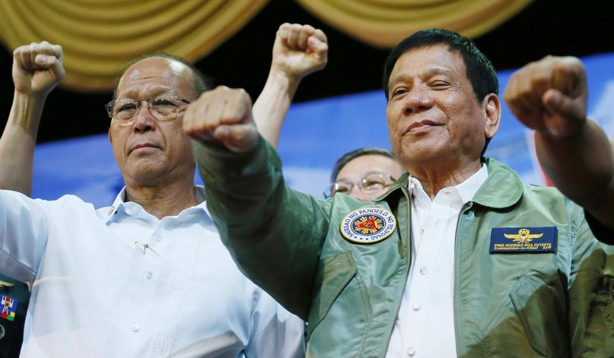 """In this Sept. 13, 2016, file photo, Philippine President Rodrigo Duterte, center, poses with a fist bump with Defense Chief Delfin Lorenzana, left, during his """"Talk with the Airmen"""" on the anniversary of the 250th Presidential Airlift Wing, at the Philippine Air Force headquarters in suburban Pasay city, southeast of Manila, Philippines. (AP Photo/Bullit Marquez, File)"""