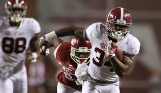 Alabama's Damien Harris runs away from an Arkansas defender during the second quarter of an NCAA college football game Saturday, Oct. 8, 2016, in Fayetteville, Ark. (AP Photo/Samantha Baker)