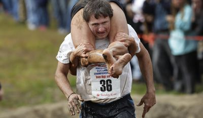 Greg Goodhue carries Wendy Hallenbeck, both of Sydney, Maine, during the North American Wife Carrying Championship, Saturday, Oct. 8, 2016, at the Sunday River Ski Resort in Newry, Maine.(AP Photo/Robert F. Bukaty)