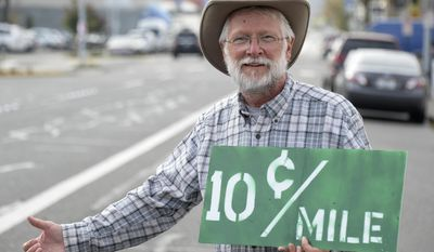 In this Thursday, Sept. 29, 2016 photo, Michael Schneider, a Lummi Island resident who hitchhikes all over the country with a pay-as-he-rides offer to drivers, poses in Bellingham, Wash. (Philip A. Dwyer/The Bellingham Herald via AP)
