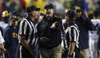 Michigan head coach Jim Harbaugh, center, complains about a call to referees during the first half of an NCAA college football game against Rutgers, Saturday, Oct. 8, 2016, in Piscataway, N.J. (AP Photo/Mel Evans)