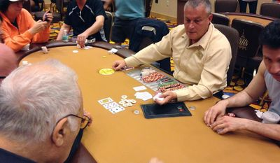 In this May, 20, 2016 photo, Eddie Aldridge, poker dealer at Trump Taj Mahal, deals out poker hands to patrons after the casino reopened the poker room in Atlantic City.  The final piece of Donald Trump's legacy in Atlantic City will close on Oct. 10, and with it will go a poker room beloved by fans of the game.  (Max Reil/The Press of Atlantic City via AP)
