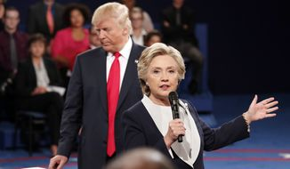 Hillary Clinton speaks as Donald Trump listens on Sunday during the second presidential debate at Washington University in St. Louis. (Associated Press)