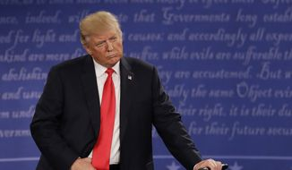 Donald Trump listens to Hillary Clinton on Sunday during the second presidential debate at Washington University in St. Louis. (Associated Press)