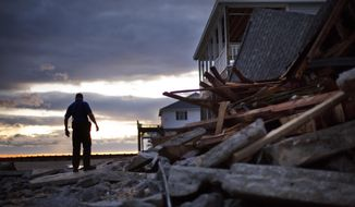 A police officer steps over the remnants of a home leveled by Hurricane Matthew after it hit the tiny beach community of Edisto Beach, S.C., Saturday, Oct. 8, 2016. (AP Photo/David Goldman)