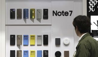 In this photo taken on Wednesday, Oct. 5, 2016, a visitor looks at  the smartphone cases of Samsung Electronics's Galaxy Note 7 at a shop in Seoul, South Korea. Samsung Electronics Co. estimated its profit rose more than expected in the July-September quarter despite the unprecedented recall of its flagship smartphones.(AP Photo/Lee Jin-man)
