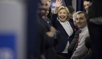 Democratic presidential candidate Hillary Clinton waves to members of the media while aboard her campaign plane at LambertSt. Louis International Airport in St. Louis, N.Y., Sunday, Oct. 9, 2016, following the second presidential debate at Washington University. (AP Photo/Andrew Harnik)