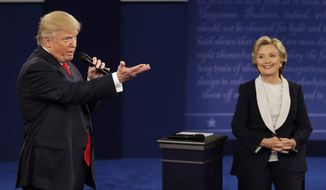 Republican presidential nominee Donald Trump speaks with Democratic presidential nominee Hillary Clinton during the second presidential debate at Washington University in St. Louis, Sunday, Oct. 9, 2016. (AP Photo/John Locher)